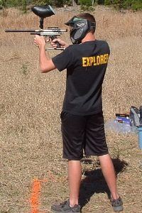 A man shooting a paintball gun.
