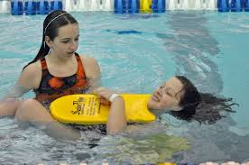 A lifeguard helping a swimmer in a pool.