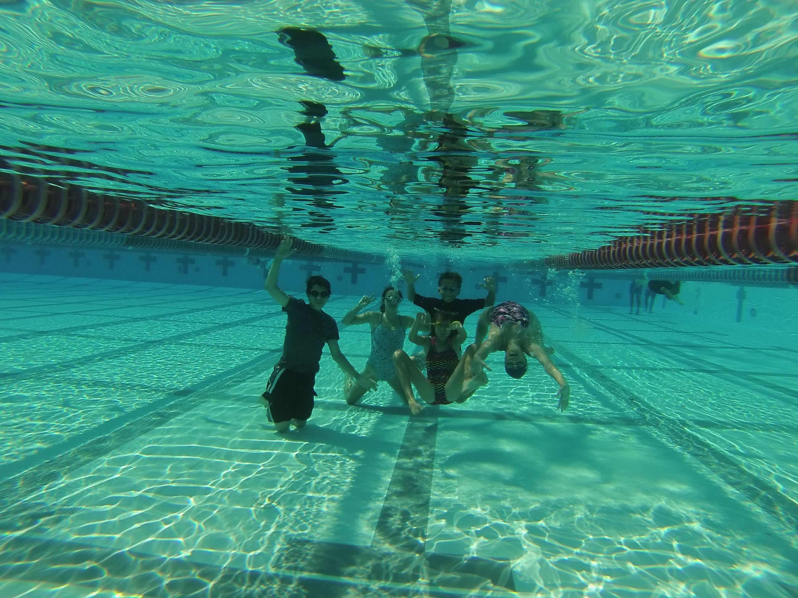 Swimmers practicing swimming under water.